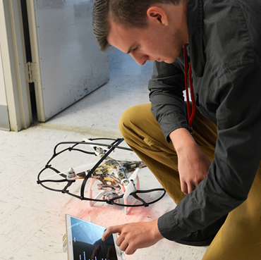 Student working on a tablet and a drone