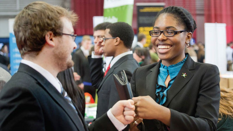 Two students fist pump at the Spring Career Fair