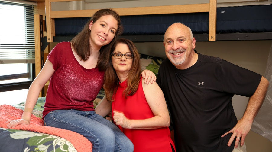 Student with parents sit on bed in dorm on move in day
